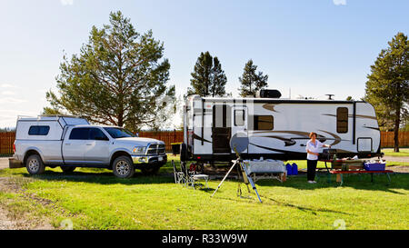 42,881.02545 woman camper traveler standing by RV camp trailer and 3/4 ton pickup truck tow vehicle, in nicely mowed green grass RV park with trees - Stock Photo