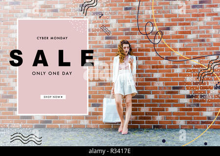shocked young woman with shopping bags using smartphone in front of brick wall, cyber monday banner - Stock Photo