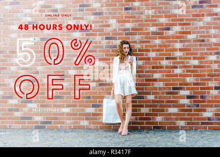 shocked young woman with shopping bags using smartphone in front of brick wall, sale banner - Stock Photo