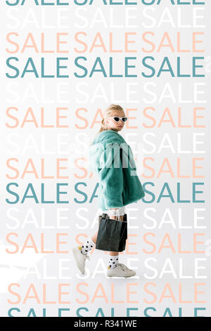 fashionable shopaholic in fur coat and sunglasses posing with black shopping bags on white, repetition of sale signs - Stock Photo