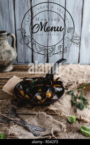 gourmet fried mussels with shells on frying pan and forks on table, healthy menu lettering - Stock Photo
