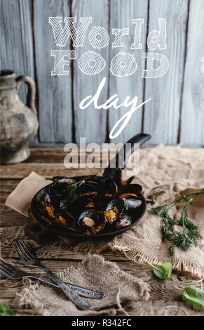 gourmet fried mussels with shells on frying pan and forks on table, world food day lettering - Stock Photo