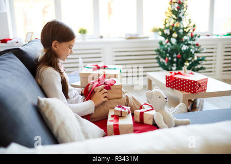 Happy child sitting on sofa and unpacking boxes with her Christmas presents - Stock Photo