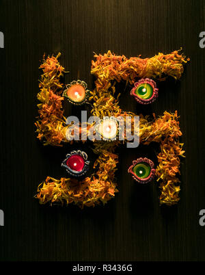 5 colourful diyas placed on table to celebrate diwali and dhanteras festival in India - Stock Photo