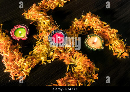 Three illuminated diya placed on swastik to celebrate diwali and dhanteras festival in India - Stock Photo