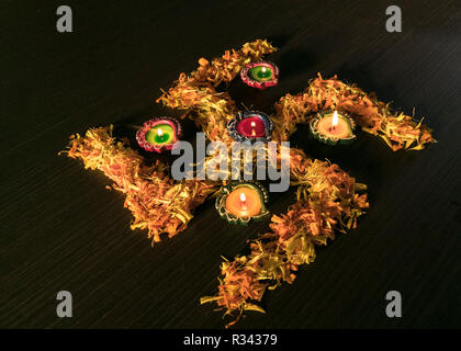 Five colourful lit diyas placed on swastik to celebrate diwali and dhanteras festival in India - Stock Photo