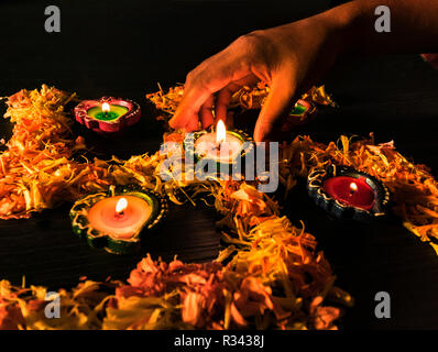 A girl lighting diyas for celebrating diwali and dhanteras festival in India - Stock Photo