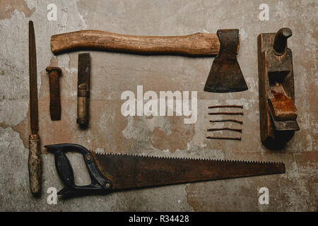 Flat lay with set of vintage rusty carpentry tools on old background - Stock Photo