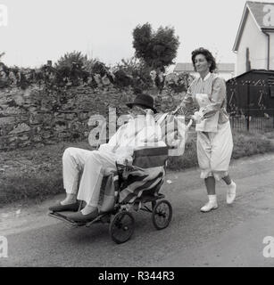 1967, pram race, Quainton, a lady dressed up as a nurse pushes a male competitor wearing hospital patient clothes, top hat and slippers, along a country road in the annual village pram race, Bucks, England, UK. - Stock Photo