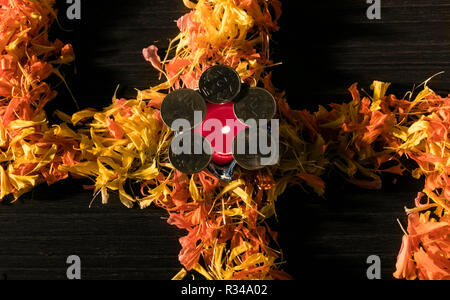 Illuminated diya placed on yellow flowers for celebrating diwali and dhanteras festival in India - Stock Photo