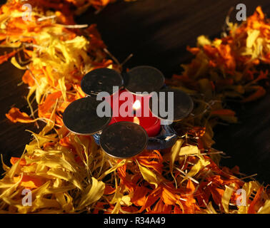 Lit diya placed on flower with coins for celebrating diwali and dhanteras festival in India - Stock Photo