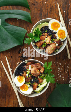 Asian food concept. Poke bowl of fried rice, chicken fillet and eggs top view - Stock Photo