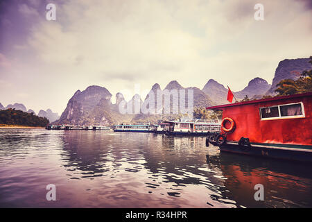 Retro toned picture of boats moored at the Lijiang River bank in Xingping. Lijiang River cruises are amongst the top China travel destinations. - Stock Photo