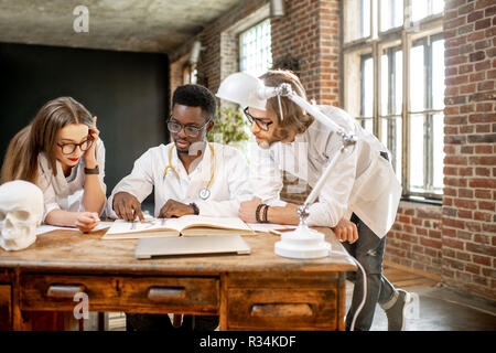 Group of a young multi ethnicity physicians or medical students in uniform working with book and drawings on the table in the office or classroom - Stock Photo