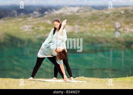 yoga teacher offers assistance in trainingparivritta