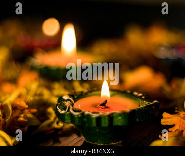 Illuminated diya paced with flowers for celebrating diwali and dhanteras in Asia - Stock Photo