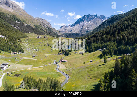 Val Grosina, Valtellina. Waterfall of Eita, green meadows and forest - Stock Photo