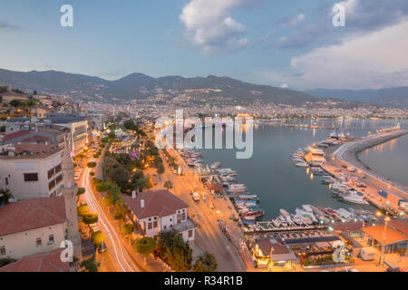 Alanya city harbor panorama in the evening with car traffic and ships and boats. Photographed from Kizil Kule (Red Tower) - main tourist attraction in - Stock Photo