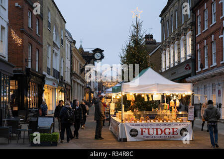 Shoppers looking at a fudge stall on Winchester High Street with a Christmas tree and lights in the background - Stock Photo