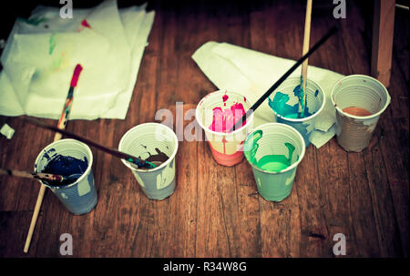 Cups with paint and brushes on the table - Stock Photo