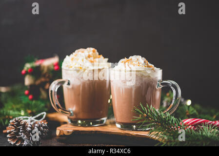 Hot chocolate with whipped cream on black background surrounded with fir tree branches. Hot Christmas drink. Comfort food for winter holidays. Copy sp - Stock Photo