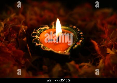 Illuminated diya placed on tablle to celebrate diwali and dhanteras - Stock Photo