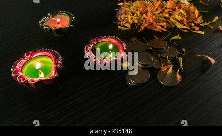Three lit diyas placed on table for diwali and dhanteras celebration in India - Stock Photo