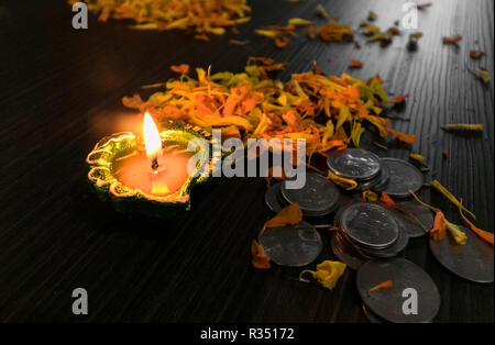 Lit diya decorated with flowers and coins for diwali and dhanteras celebration in India - Stock Photo