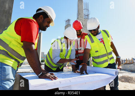 Men with Blueprints in hand are working in the construction Industry and wearing hard hat and safety vest, they stay together under the blue sky and s - Stock Photo