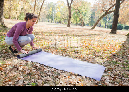 Fit woman rolling yoga mat at autumn park in the morning. Sporty girl prepare for exercise. - Stock Photo