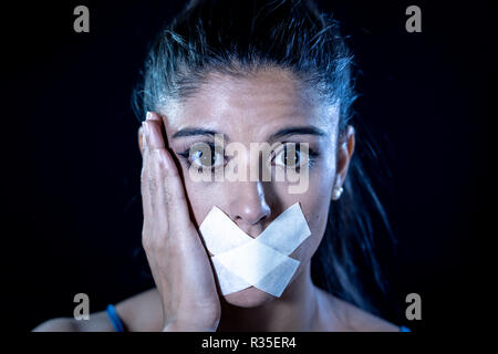 Attractive scared woman with taped mouth making in Silence Abuse Censorship Me too and Freedom of speech Concept Isolated on black background. - Stock Photo
