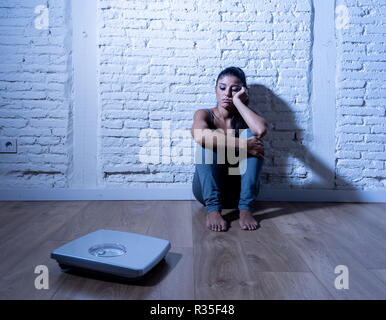 Young anorexic teenager woman sitting alone on ground looking at the scale worried and depressed in dieting and eating disorder concept - Stock Photo