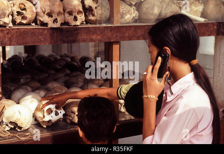10.03.2005, Phnom Penh, Cambodia, Asia - A young woman is talking on the phone as she looks at the human skulls of the victims of the Pol Pot regime. - Stock Photo