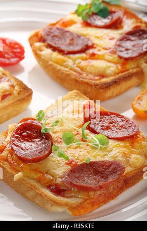 Toasts with melted cheese and fried sausage, breakfast on the plate - Stock Photo