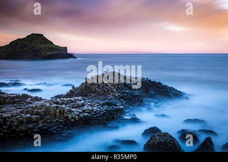 Long exposure of dawn breaking across The Giant's Causeway in Bushmills, Northern Ireland - Stock Photo