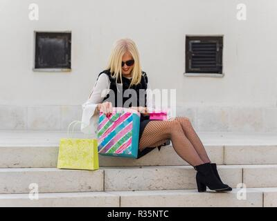 Mid-adult senior pretty woman blonde hair looking down into paper bag serching look for something inside in there - Stock Photo