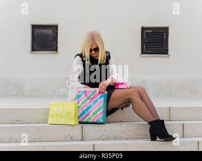 Mid-adult senior pretty woman blonde hair looking down into paper bag searching look for something inside in there - Stock Photo
