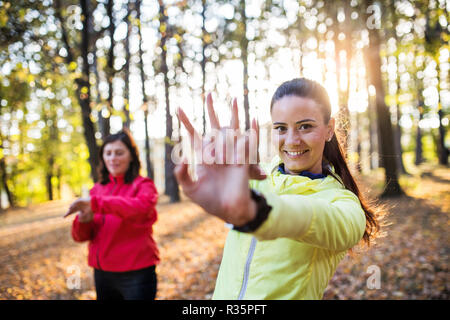 Two female runners stretching outdoors in forest in autumn nature. - Stock Photo