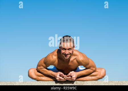 Yoga practice helps find harmony and balance. Man practicing yoga blue sky background. Reached peace of mind. Meditation and yoga concept. Yoga helps find balance and unite with nature. - Stock Photo