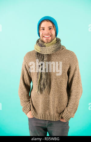 Man wear knitted clothes turquoise background. Winter accessories concept. Winter fashion knitted clothes. Knitted accessories as hat and scarf. Man in knitted hat and scarf winter fashion season. - Stock Photo