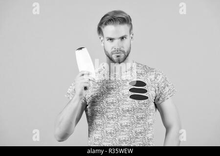 Man strict face holds shampoo bottle, grey background. Man enjoy freshness after washing hair with shampoo. Hair care and beauty supplies concept. Guy with hairstyle holds bottle shampoo, copy space. - Stock Photo