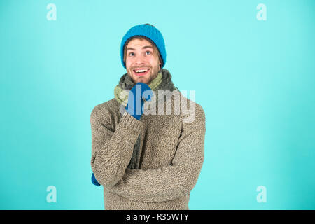 Winter accessories concept. Winter fashion knitted clothes. Knitted accessories as hat and scarf. Man knitted hat gloves and scarf winter fashion. Man wear knitted accessory turquoise background. - Stock Photo