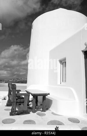 Table and bench in yard of Mykonos, Greece. House on mountain landscape, architecture. Building with whitewashed walls on blue sky. Summer vacation on mediterranean island. Travel and journey concept. - Stock Photo