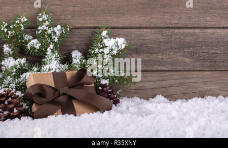 Christmas present wrapped in brown paper and ribbon with pine cones and evergreen tree branches on snow against a rustic wooden background - Stock Photo