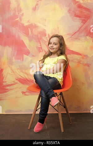 kid or small smiling girl sitting on orange chair on colorful abstract background in jeans and tshirt with long blond hair
