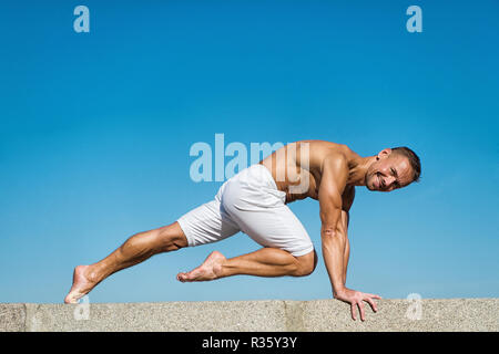 Man practicing yoga blue sky background. Reached peace of mind. Meditation and yoga concept. Yoga helps find balance. Practice asana outdoor. Yoga practice helps find harmony and balance. - Stock Photo