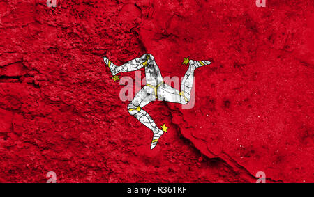 Flag of Isle Of Man close up painted on a cracked wall, concept of armed actions and conflicts in the world - Stock Photo