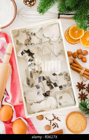 Holiday food background. Christmas cookie cutters, rolling pin and ingredients for baking on white wooden table. Top view. - Stock Photo