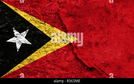 Flag of East Timor close up painted on a cracked wall, concept of armed actions and conflicts in the world - Stock Photo