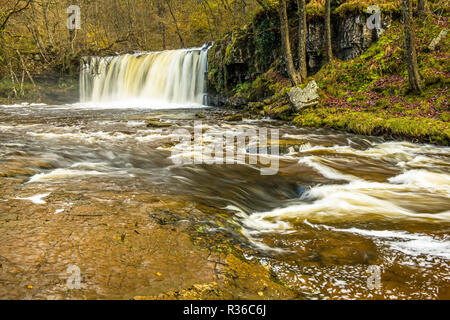 The Upper Ddwli waterfall on the River Neath in the Vale of Neath on an autumn winter day after heavy rain. - Stock Photo